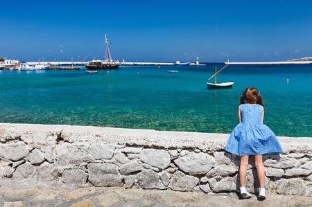 Vista posterior de un poco de vistas chica disfrutando del mar Mediterráneo en la isla de Mykonos, Grecia