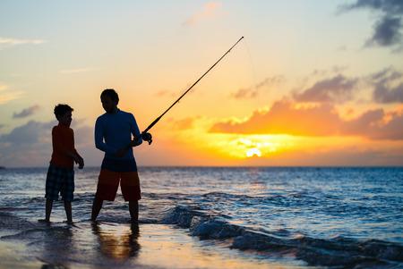 Padre e hijo juntos de pesca en el océano de la playa de la puesta del sol Foto de archivo
