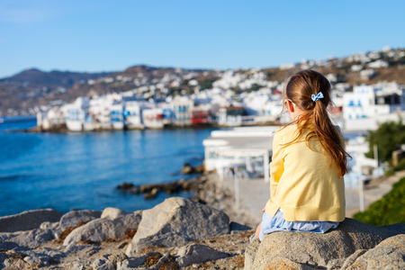 unrecognisable person: Back view of little girl enjoying views of traditional white village on Mykonos island, Greece Stock Photo