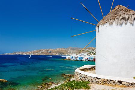 mykonos: White greek windmills overlooking Little Venice popular tourist destination at traditional village on Mykonos Island, Greece, Europe
