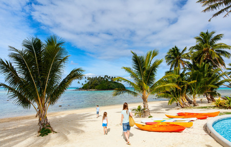 south pacific ocean: Family  at beautiful tropical beach with palm trees, white sand, turquoise ocean water and blue sky at Cook Islands, South Pacific