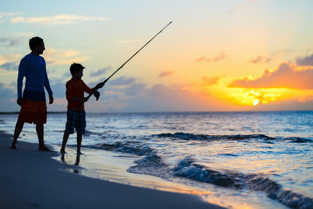 ocean fishing: Father and son fishing together in ocean from beach on sunset