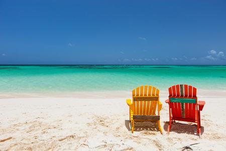silla de madera: Adirondack sillas de colores amarillo y naranja en la playa tropical en el Caribe con hermosa agua de mar azul turquesa, arena blanca y azul cielo