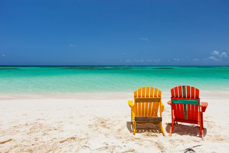chair wooden: Colorful adirondack yellow and orange lounge chairs at tropical beach in Caribbean with beautiful turquoise ocean water, white sand and blue sky