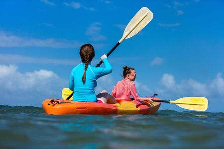 Familie von Mutter und Tochter Paddeln auf Kajaks am tropischen Meerwasser während der Sommerferien