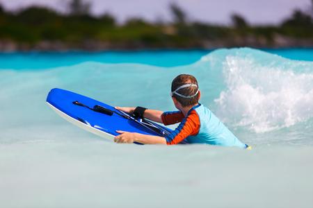 boogie: Little boy on vacation having fun swimming on boogie board