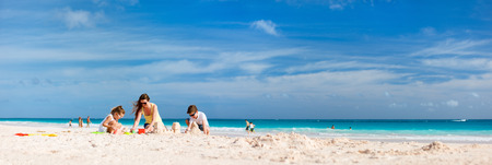 jovenes felices: Madre y niños que hacen castillos de arena en la playa tropical Foto de archivo