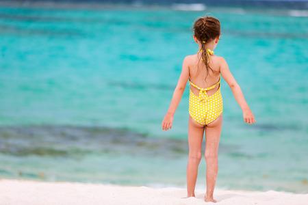traje de baño: Volver la vista de una niña en la playa durante las vacaciones de verano