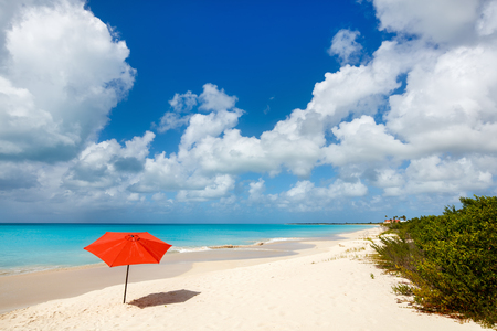 desolated: Red umbrella on Idyllic tropical beach with white sand, turquoise ocean water and blue sky at deserted island in Caribbean