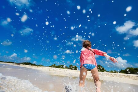 cute little girl: Happy little girl running and splashing at shallow water at beach having a lot of fun on summer vacation