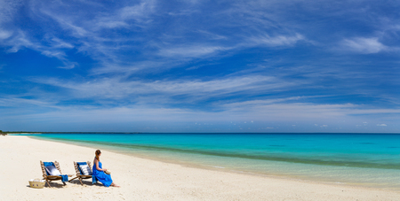 beach panorama: Back view of a young beautiful woman relaxing at white sand tropical beach panorama Stock Photo