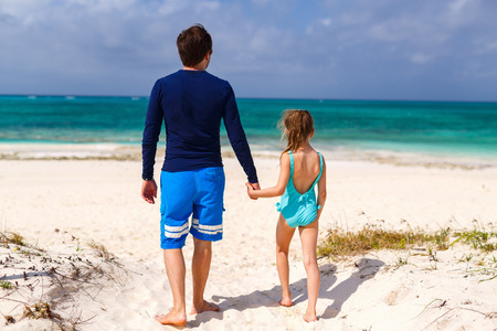 view girl: Father and his adorable little daughter at beach