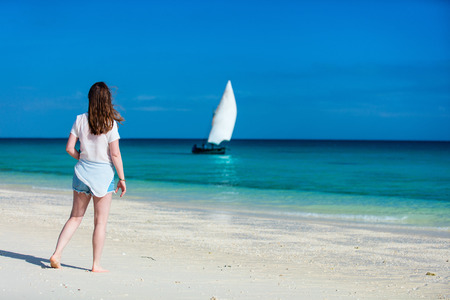 view woman: Back view of a young beautiful woman at white sand tropical beach looking at traditional african boat Stock Photo