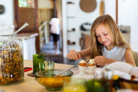 레스토랑에서 아침 식사 삶은 계란을 먹고 사랑스러운 작은 소녀