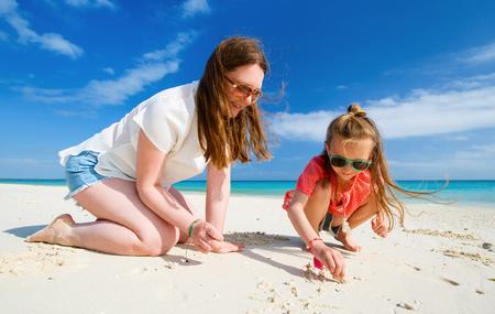 mama e hija: Madre e hija disfrutando de vacaciones en la playa tropical