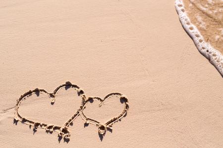 luna de miel: Corazones dibujados en la arena de playa y las olas del mar Foto de archivo