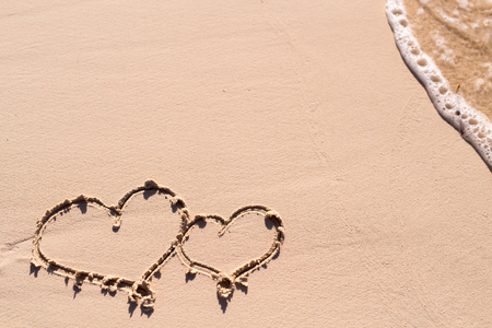 honeymoon: Hearts drawn on beach sand and sea wave Stock Photo