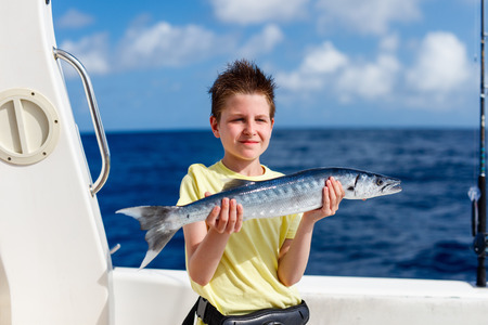 Lucky teenage boy holding barracuda proud with the catch on boat deck Фото со стока - 63982431