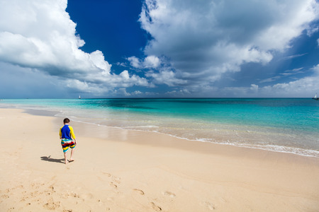 sun protection: Teen age boy in sun protection rash guard at tropical beach on summer vacation Stock Photo