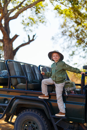 game drive: Adorable little girl in South Africa on morning game drive near open vehicle