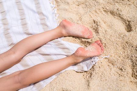 girl legs: Close up of a little girl legs on a beach towel