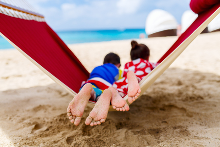 Brother and sister kids relaxing in hammock at tropical beach Stock Photo