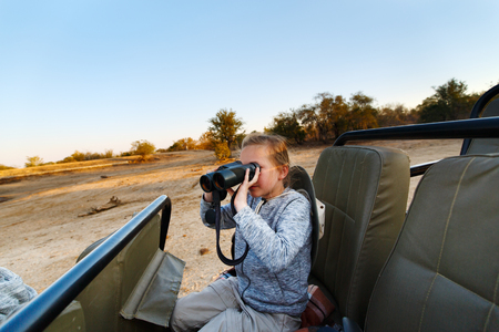 game drive: Adorable little girl in South Africa on morning game drive in open vehicle Stock Photo