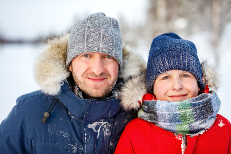 Family of father and his son outdoors on beautiful winter snowy day