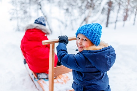 Adorable little girl and cute boy outdoors on Christmas day having fun playing in snow