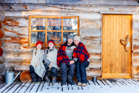 casa de campo: Family with kids outdoors on beautiful winter day in front of log cabin vacation house Foto de archivo