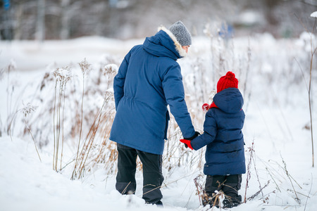 Back view of family father and his adorable little daughter outdoors on beautiful winter snowy day Stock Photo