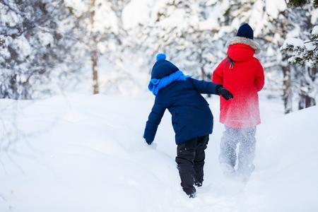 detras de: Vista posterior de la niña y del muchacho lindo al aire libre en el hermoso día de invierno que se divierten jugando en la nieve Foto de archivo