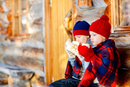 Kids outdoors on beautiful winter day drinking hot chocolate in front of log cabin vacation house Banque d'images