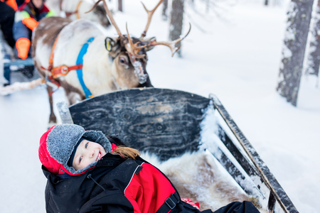 winter finland: Little girl at reindeer in winter forest in Lapland Finland