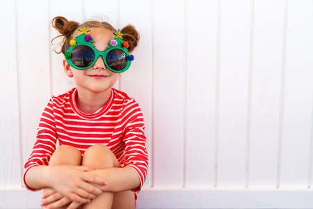 Adorable little girl in a funny Christmas glasses over white background Imagens