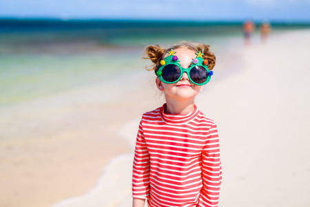 christmas funny: Adorable little girl in a funny Christmas glasses at tropical beach Stock Photo