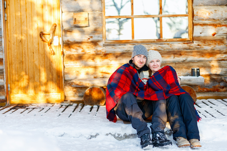 december: Couple outdoors on beautiful winter day in front of log cabin vacation house