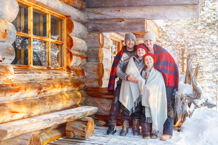 cottage: Family with kids outdoors on beautiful winter day in front of log cabin vacation house Stock Photo