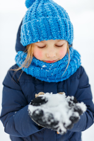 Adorable little girl wearing warm clothes outdoors on beautiful winter snowy day Stock Photo