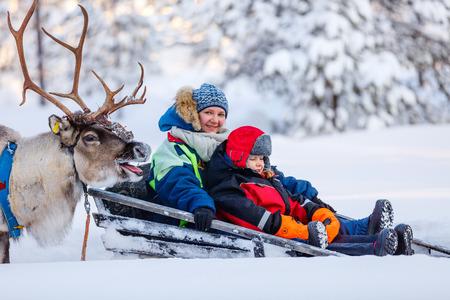 Familie der Mutter und kleine Mädchen auf Rentiersafari im Winter Wald in Lappland Finnland