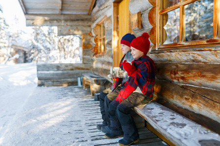 Kids outdoors on beautiful winter day drinking hot chocolate in front of log cabin vacation house Stock Photo