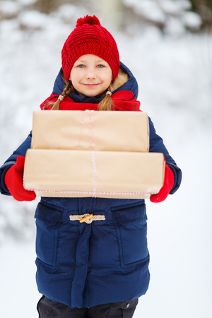 Adorable little girl wearing warm clothes outdoors on Christmas day holding gifts Stock Photo