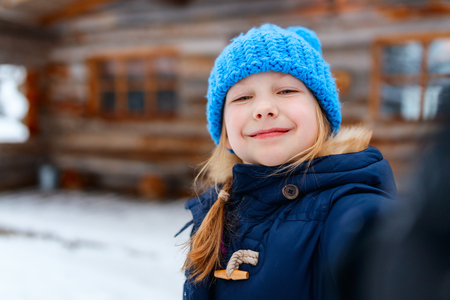 Little girl outdoors on beautiful winter day in front of log cabin vacation house