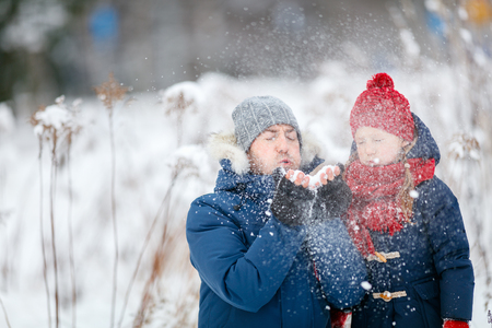 Family of father and his adorable little daughter outdoors on beautiful winter snowy day
