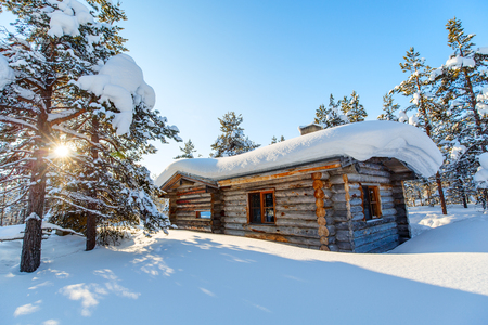 Beautiful winter landscape with wooden hut and snow covered trees Standard-Bild
