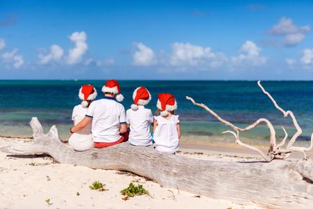 Vista trasera de la hermosa familia que lleva sombreros rojos de Santa en la playa tropical celebrar la Navidad Foto de archivo