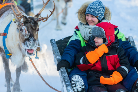 Family of mother and little girl at reindeer safari in winter forest in Lapland Finland
