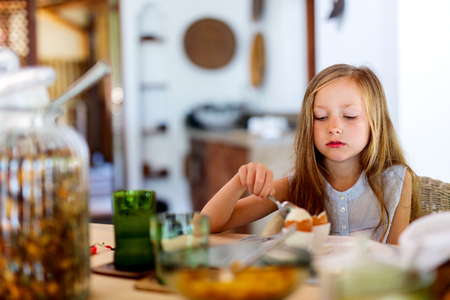 bacon portrait: Adorable little girl eating boiled egg for a breakfast in restaurant