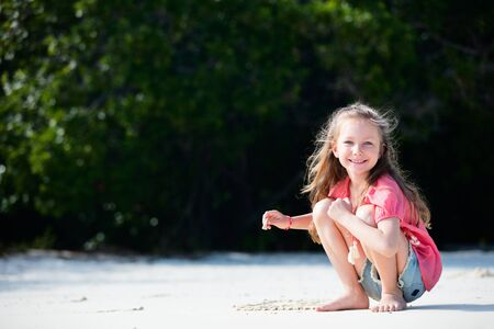 Adorable little girl at beach during summer vacation
