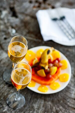 Two glasses with champagne  and fruits on wooden vintage tray served for special occasion or celebration Stock Photo